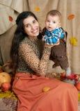 Jesieni kobieta z chłopiec na żółtych spadków liściach, jabłka, bania, dekoracja na tkaninie, szczęśliwa rodzina i kraju pojęcie, Obraz Stock