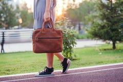 Jesieni mody uliczny spojrzenie Młoda brunetki dziewczyna w szarość dziającej długiej sukni z wielką jaskrawą pomarańczową rzemie Zdjęcie Royalty Free