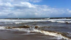 Jesieni plaża z niebieskim niebem, chmurami i dużymi fala, zdjęcie stock