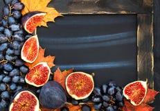 Jesieni rama z kredową deską, liśćmi, figami i winogronem, astronautyczny fo Zdjęcia Stock