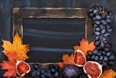 Jesieni rama z kredową deską, liśćmi, figami i winogronem, astronautyczny fo Zdjęcie Royalty Free
