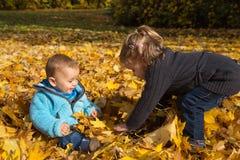 Jesieni rzecz: brat i siostra ma zabawę w jesieni bawić się dowcip zdjęcia stock