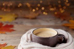 Jesieni tło od filiżanki kakao lub kawy w trykotowym szaliku na drewnianym stole dekorującym z spadkiem opuszcza Wygodny gorący n obraz royalty free