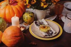 Jesieni tradycyjny sezonowy stołowy ustawiać w domu z baniami, świeczkami i kwiatami, obraz stock