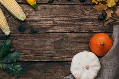 Jesieni warzywa: banie i kukurudza z kolorów żółtych liśćmi na drewnianym tle zdjęcie royalty free