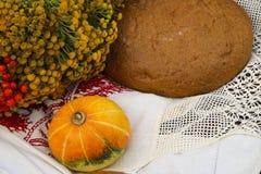 Jesieni wciąż życie - bochenek, bania, halny popiół, tansy, pszeniczni ucho, sól, na białym tablecloth z koronką Zdjęcie Stock