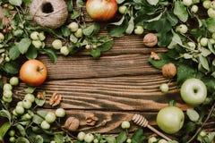 Jesieni wygodny flatlay ramowy przygotowania z jabłoni gałąź, dojrzałymi owoc, łyżką, orzechami włoskimi i dratwą na drewnianym, obraz stock