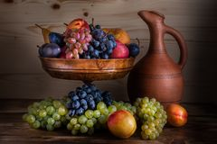 Jesienny owoc wciąż życie z Gruzińskim dzbankiem na nieociosanej drewnianej zakładce zdjęcie stock