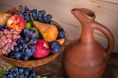 Jesienny owoc wciąż życie z Gruzińskim dzbankiem na nieociosanej drewnianej zakładce Fotografia Royalty Free