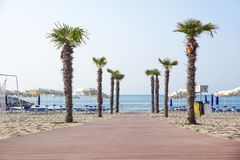 JESOLO ITALIEN 02, JUNI 2017: Fot- gångbana som sätter på land tillträde med palmträd Det Queso systemet är den bästa vägen att f Royaltyfria Bilder