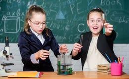 Jest ostrożnego spełniania chemicznym reakcją r Dziewczyny nauki chemia Robi studiowanie chemii obrazy royalty free