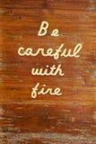 Jest Ostrożny Z Pożarniczym Drewnianym znakiem Zdjęcie Stock
