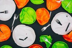 Jest plastikowy bezpłatny Używa kolorowych łamających plastikowych talerze i rozwidlenia na ciemnym tle Przerwa klingerytu zaniec obrazy royalty free