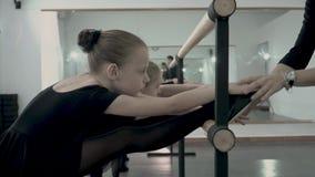 Jest rozciągliwości noga na barre ostrożnie poprawnych blisko do małej baleriny ubierającej w czarnym leotard baletniczym nauczyc zbiory wideo