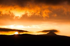 Jested Mountain hidden in the clouds. Dramatic red sky at sunset time. Liberec, Czech Republic.  Stock Image