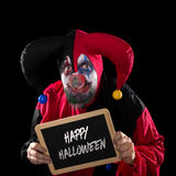 Jester holding a slate with text happy halloween, black backgrou Stock Images