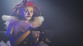 Frowning clown woman with white and black old makeup and a red hat, slow motion stock video