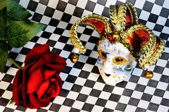 The jester mask carnival and flower red rose Queen of flowers on the background of a chessboard. The mask is a symbol of transformation, change and at the same royalty free stock photos