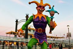 Jester by Riverboat. New Orleans Jester on the boardwalk by a paddle boat on the river Royalty Free Stock Images