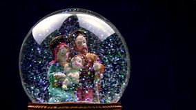 Jesus baby. Black background. Joseph and Mary with baby Jesus in her arms. Glass ball with toy figures on a black background. The blizzard of multicolored