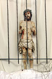 Jesus behind bars in prison. Wooden figure of Jesus in the churc Royalty Free Stock Photo