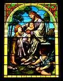 Jesus Blesses Children. A stained glass window depicting Jesus blessing the children by holding one toddler in his lap and laying his and on another child's head Royalty Free Stock Images
