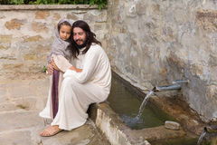 Jesus blessing a little girl. Biblical scene when Jesus says, let the little children come to me, blessing a little girl. Historical reenactment at an old water Royalty Free Stock Image
