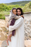 Jesus carrying a little girl. Biblical scene when Jesus says, let the little children come to me, blessing a little girl. Historical reenactment at an old water Stock Photography