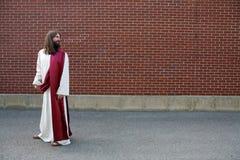 Jesus che esamina sopra la sua spalla la parete in bianco Fotografia Stock