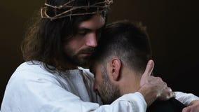 Jesus Christ amável que abraça o pobre homem isolado no fundo escuro, remissão vídeos de arquivo