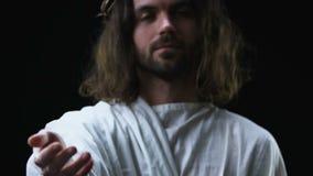Jesus Christ amável que estica a mão amiga contra o fundo escuro, cristandade video estoque