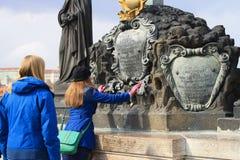 Jesus Christ auf querer statuarischer Gruppe auf Charles-Brücke in Prag mit Touristen lizenzfreie stockbilder