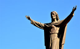 Jesus. A bronze statue of Jesus on the top of a church watching over all of his creations and parishioners among his majestic blue clear sky Stock Photo