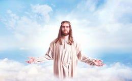 Jesus Christ com os braços abertos contra o céu nebuloso imagem de stock