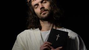 Jesus Christ com os olhos fechados na coroa da Bíblia da terra arrendada dos espinhos, crucificação filme