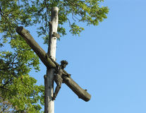 Jesus Christ on Cross. Wooden old sculpture against blue sky. Tree in background. Space for additional text/graphics Royalty Free Stock Photos