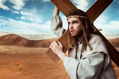 Jesus Christ with cross in desert, cloudy sky. On background. The great martyr with crucifixion, symbol of christian religion Stock Image