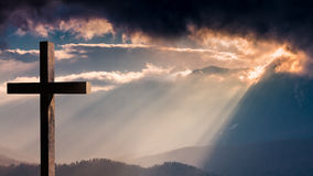 Jesus Christ cross. Easter, resurrection concept. Christian cross on a background with dramatic lighting, colorful mountain sunset, dark clouds and sky and Royalty Free Stock Photo