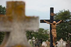 Jesus Christ on cross imposing in cimitir. Jesus Christ on cross surrounded by tombstones in cemetery Stock Photography