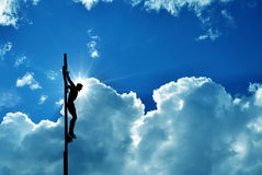 Jesus Christ on the cross over blue dramatic sky background Royalty Free Stock Images