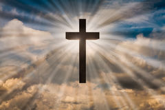Jesus Christ cross on a sky with dramatic light, clouds, sunbeams. Easter, resurrection, risen Jesus concept Stock Images