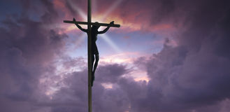 Jesus Christ on the Cross. With sunset clouds as a background royalty free stock images