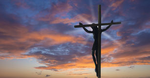 Jesus Christ on the Cross. With sunset clouds as a background Stock Photo