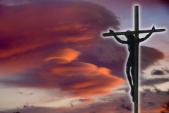 Jesus Christ on the Cross. With sunset clouds as a background Stock Photos