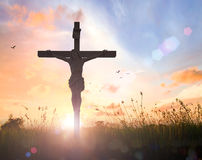 Jesus Christ on the cross on sunset. Silhouette Jesus Christ and the cross on blurred beautiful autumn sunset with amazing light background Stock Images