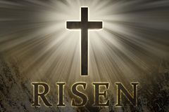 Jesus Christ cross surrounded by light and risen text on a rock background for Easter. Wooden Christian cross elevated, raised up in the sky, surrounded by Royalty Free Stock Photography