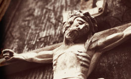 A wooden sculpture of crucified Jesus Christ  styled retro. Jesus Christ crucified an ancient wooden sculpture details Royalty Free Stock Photography