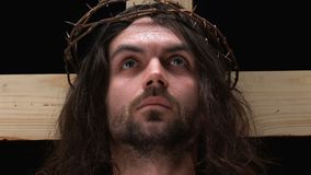 Jesus Christ crucified on cross and looking to heaven, praying father, close-up. Stock footage stock footage