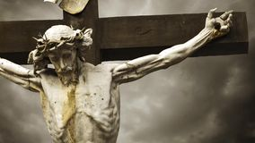 Jesus Christ crucified. The Crucifixion. Christian cross with Jesus Christ statue over stormy clouds time lapse. 1920x1080