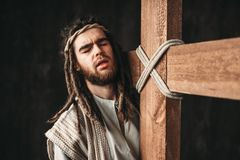Jesus Christ with crucifixion on black background. Holy Jesus Christ with crucifixion on black background. Great martyr with cross, christianity symbol Stock Photo